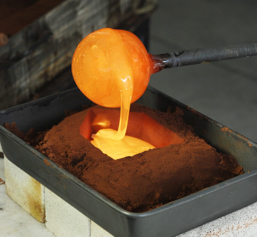 Molten glass being poured into an impression in a tray of sand.