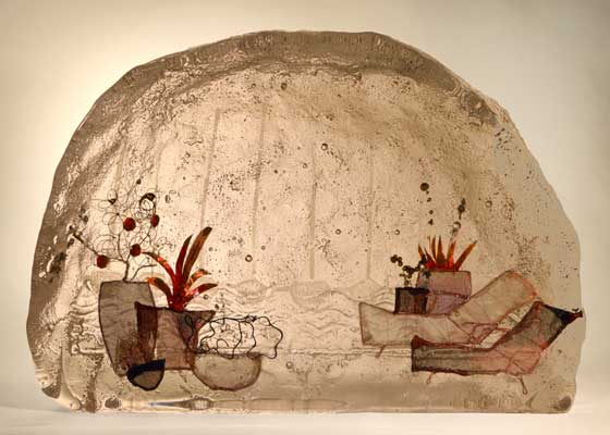 Sandcast glass scene with wire inclusions. Garden loungers and plant pots with boat detail in background.